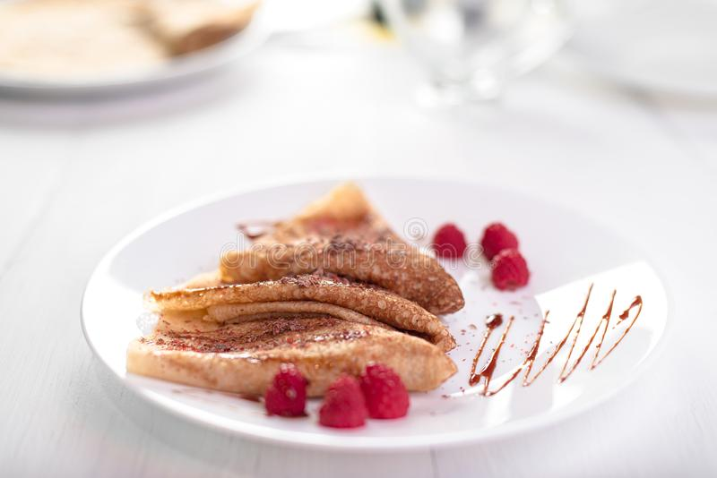 三个俄国稀薄的薄煎饼和绉纱折叠了三角用莓、焦糖调味汁和巧克力片 免版税库存图片