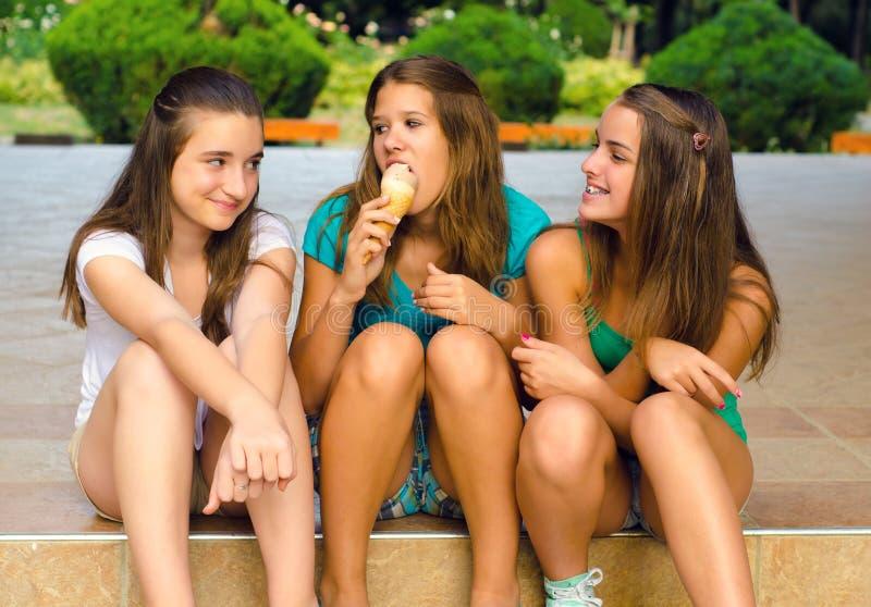 三个十几岁的女孩和一冰淇凌 免版税库存图片