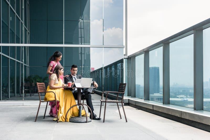 三个印地安商人谈话在断裂期间在工作 免版税库存图片