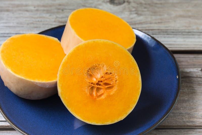 三个厚片在蓝色板材的明亮的橙色胡桃南瓜 免版税库存照片