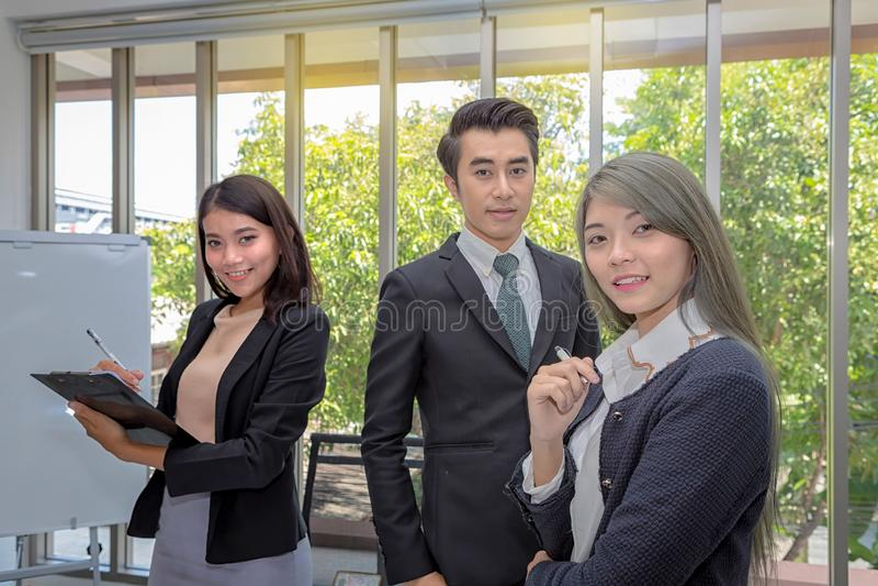 三个商人在候选会议地点 摆在候选会议地点的亚洲事务队在办公室 在宽敞的运作的激发灵感 库存图片