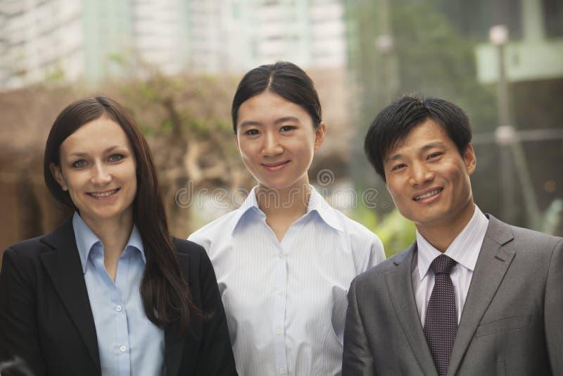 三个商人,不同种族的小组画象  免版税库存图片