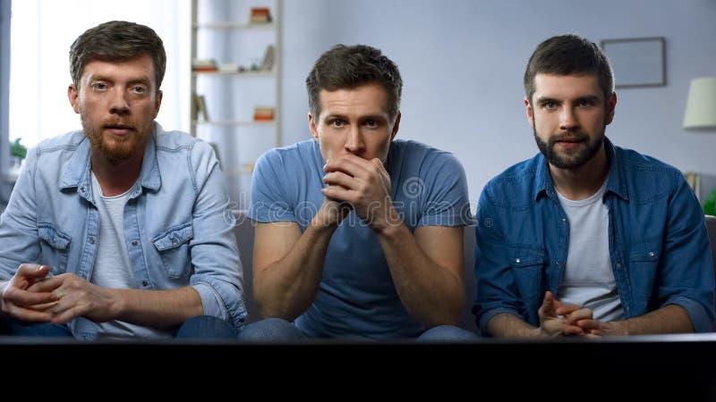 三个在电视的最好的朋友观看的体育竞赛在家,享受好比赛 图库摄影
