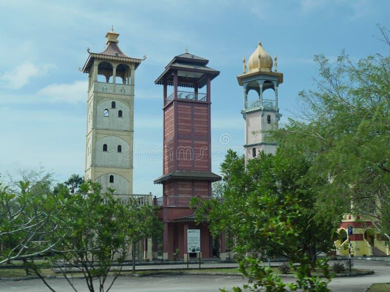 三个塔在Melaka门户曲拱附近肩并肩站立在Melaca,马来西亚代表三主要种族在国家 库存图片
