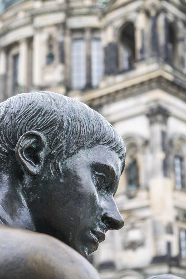 三个女孩一个男孩雕象,男孩的面孔的细节与大教堂的在背景中 库存图片