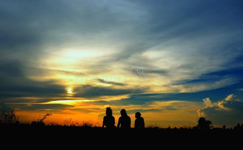 三个女孩剪影坐草在日落 库存照片