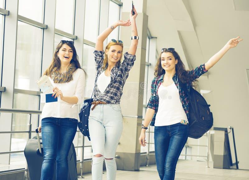 三个女孩努力去做与他们的行李在机场并且笑 与朋友的一次旅行 免版税库存图片