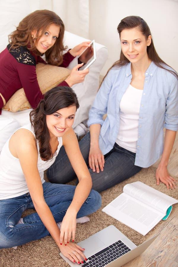 三个女孩和膝上型计算机 库存照片