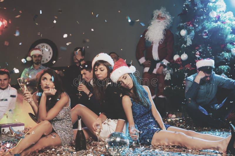 三个女孩坐地板和乏味 他们在一个喧嚣的党以后是非常疲乏新年 免版税库存照片