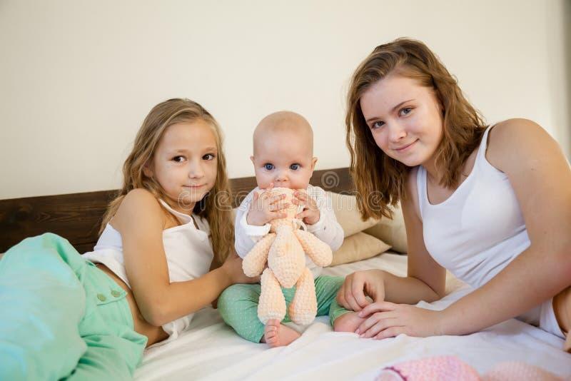 三个女孩早晨使用在卧室 库存照片