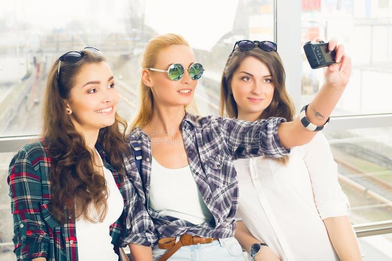 三个女孩站立在机场和看片剂 与朋友的一次旅行 做selfie的女孩 免版税库存图片
