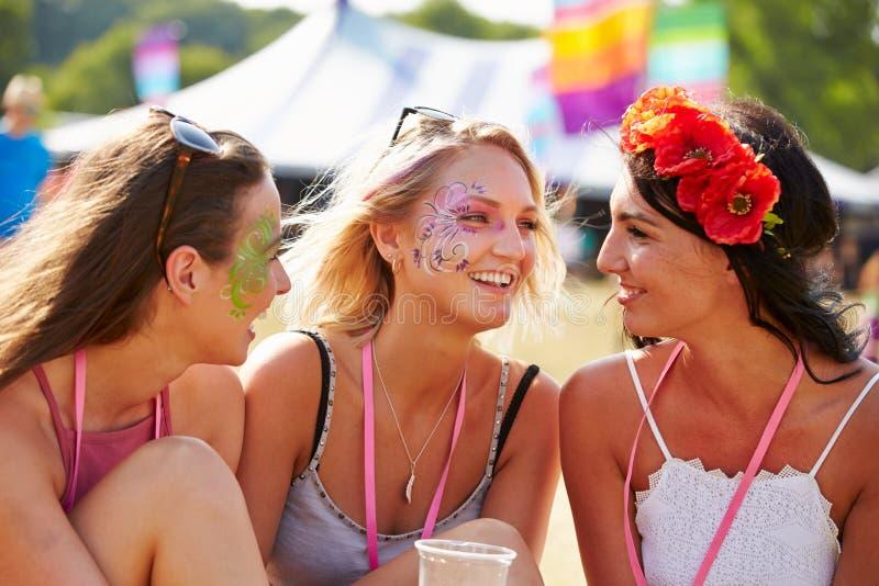 三个女朋友谈话在音乐节 免版税库存图片