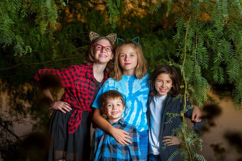 三个姐妹和他们的兄弟在一低垂悬的树摆在下 库存照片