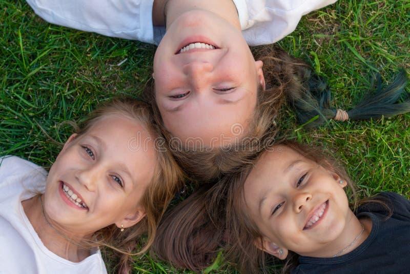 三个姐妹夏天画象 逗人喜爱的女孩在草和微笑说谎 室外微笑的孩子 夏天的概念 图库摄影