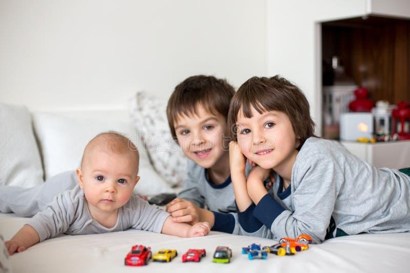 三个孩子、婴孩和他的更老的兄弟在床上在mornin 免版税图库摄影