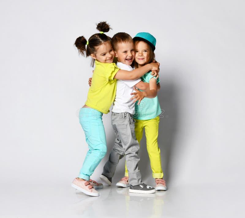 三个孩子充分的身体射击明亮的衣裳、两个女孩和一个男孩的 三胞胎、兄弟和姐妹 库存照片