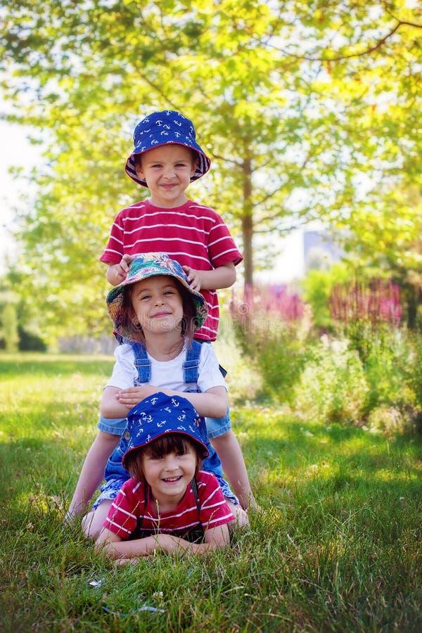 三个孩子在公园,站立一在其他,微笑 库存照片