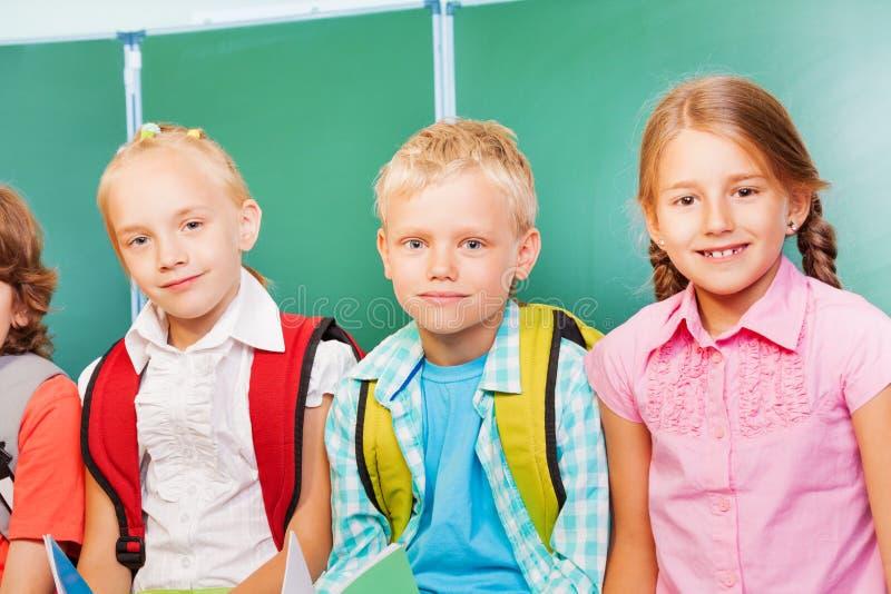 三个孩子在黑板前面一起站立 免版税库存图片