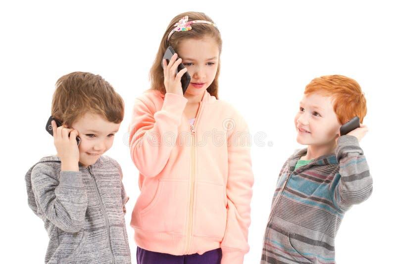 三个孩子谈话在孩子手机 库存图片