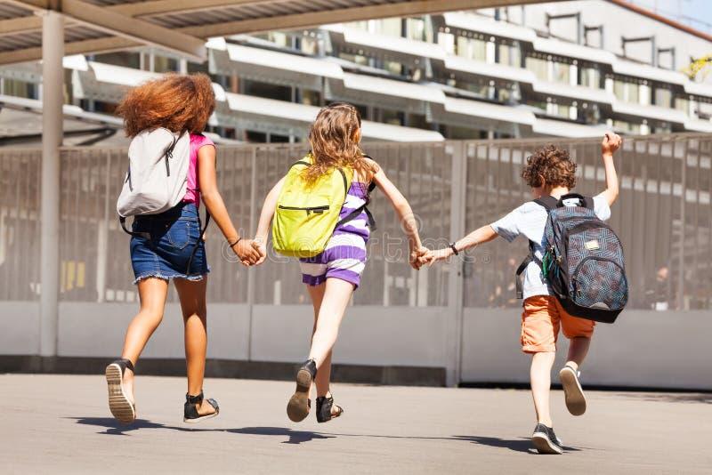 三个孩子跑到学校视图从后面 免版税库存图片