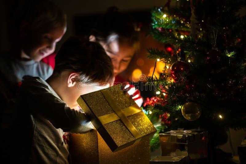 三个孩子,两个小孩男孩和女孩,打开一件金黄礼物b 库存图片