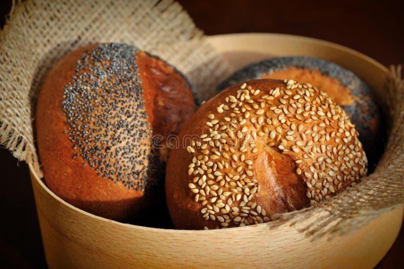 三个小圆面包用芝麻和罂粟种子在粗麻布 免版税库存照片