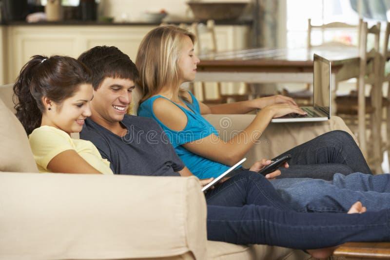 三个少年在家坐沙发使用手机、片剂计算机和膝上型计算机 免版税图库摄影