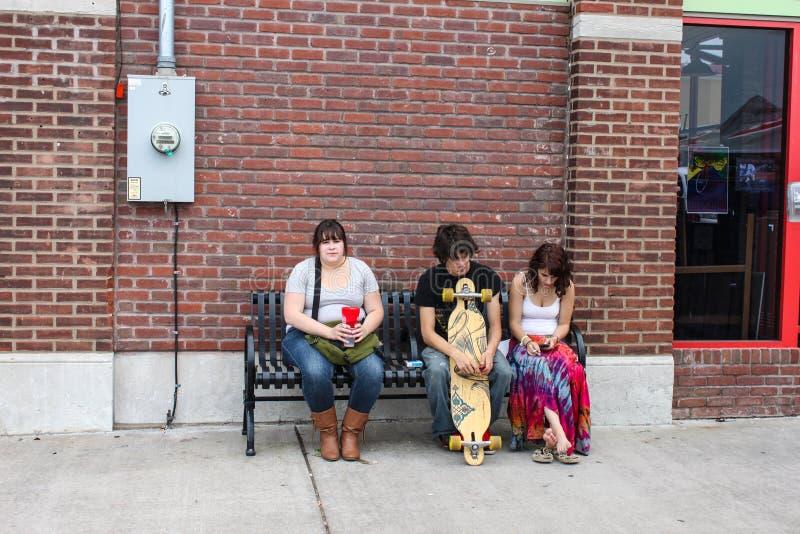 三个年轻成人坐都市长凳土尔沙大约2010年5月的俄克拉何马美国 免版税图库摄影