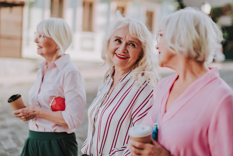 三个年长女性朋友在城市走 免版税库存照片