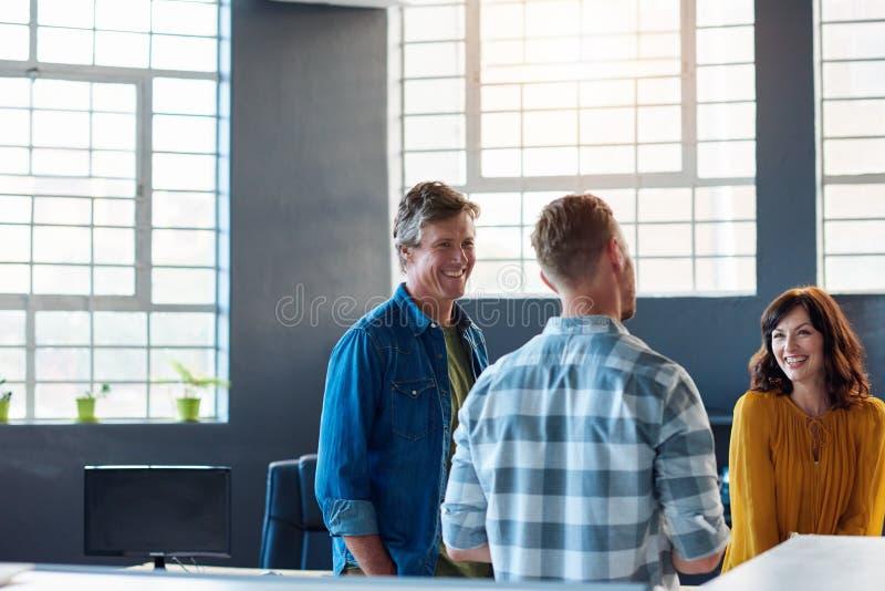 三个微笑的同事一起谈话在一个现代办公室 免版税图库摄影