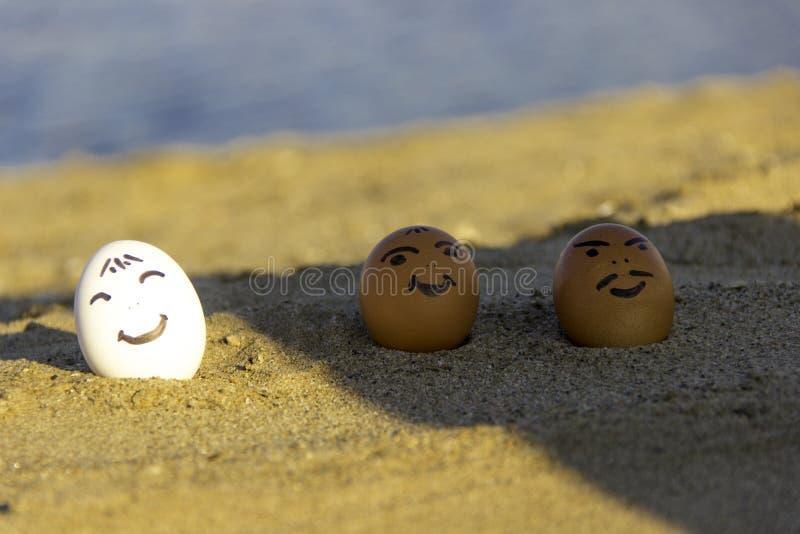 三个微笑的鸡鸡蛋在海滩晒日光浴 库存照片