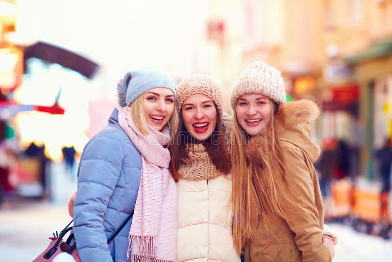 三个愉快的女孩,朋友画象一起在冬天街道上 库存照片