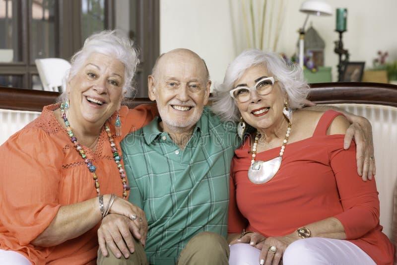 三个愉快的资深朋友坐长沙发 免版税图库摄影