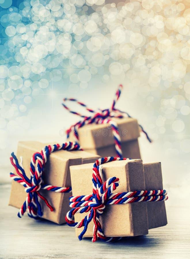 三个手工制造礼物盒在发光的颜色圣诞节背景中 免版税库存图片