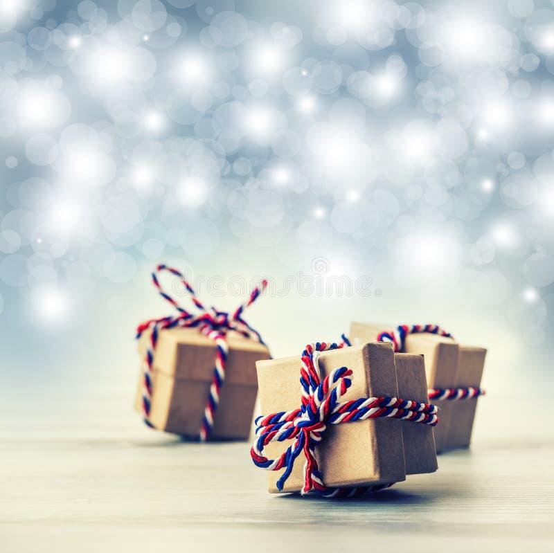 三个手工制造礼物盒在发光的颜色背景中 免版税库存照片