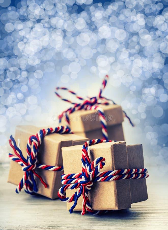 三个手工制造礼物盒在发光的颜色背景中 库存图片