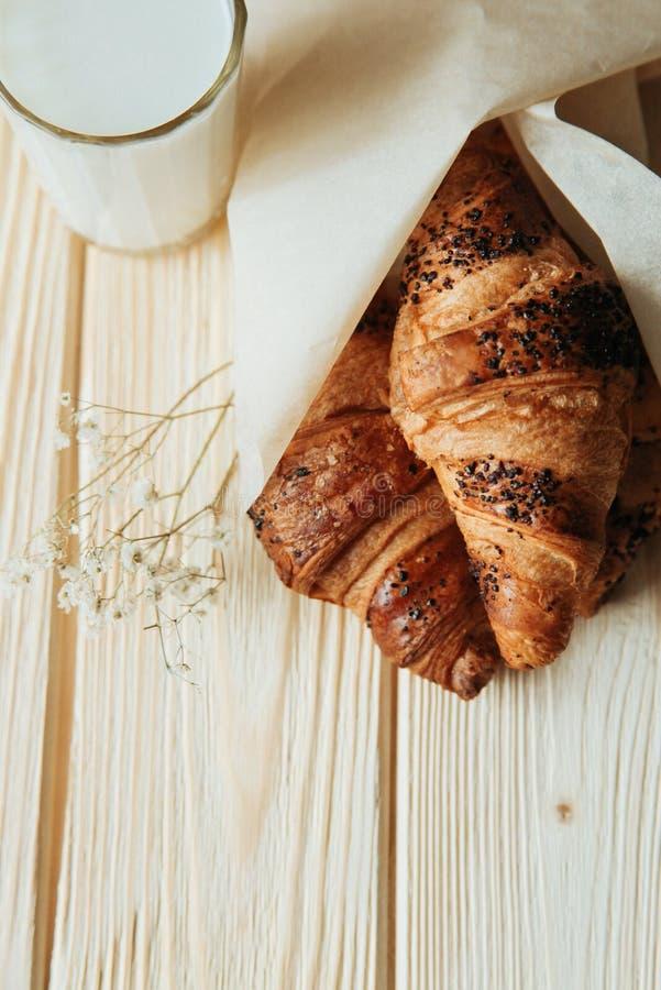 三个新月形面包用巧克力和牛奶在木桌上 库存图片