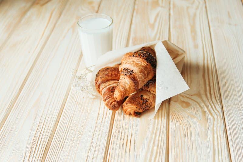 三个新月形面包用巧克力和牛奶在木桌上 免版税库存图片