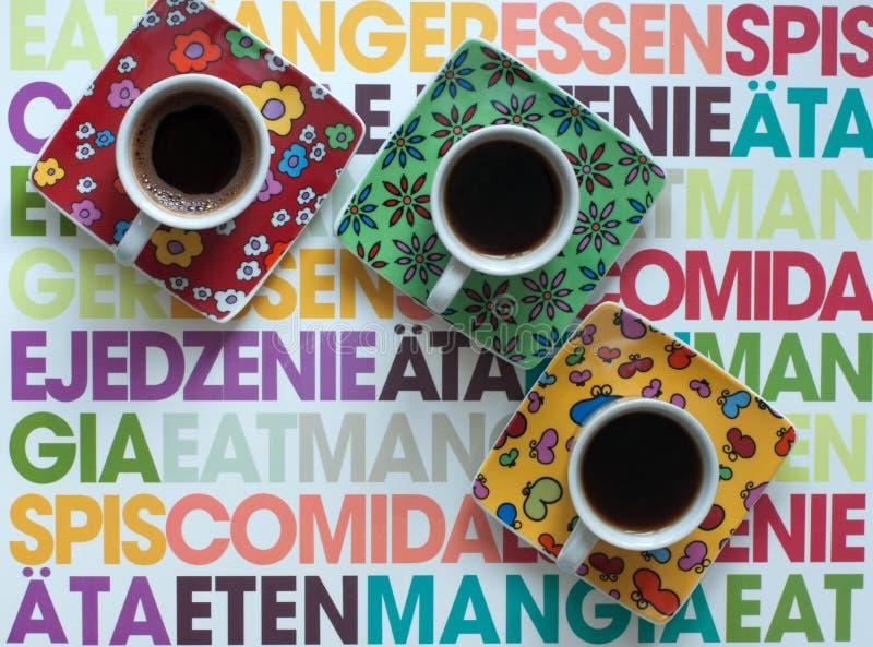 三个明亮的咖啡杯用五颜六色的表面上的热的浓咖啡 库存图片
