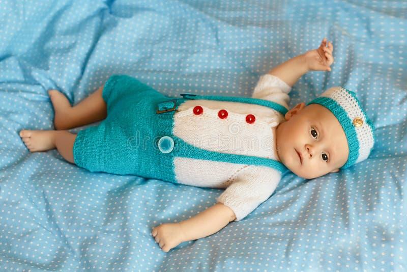 三个月男婴的画象一套蓝色被编织的衣服的在一条蓝色毯子在托儿所屋子里 平的位置 库存照片
