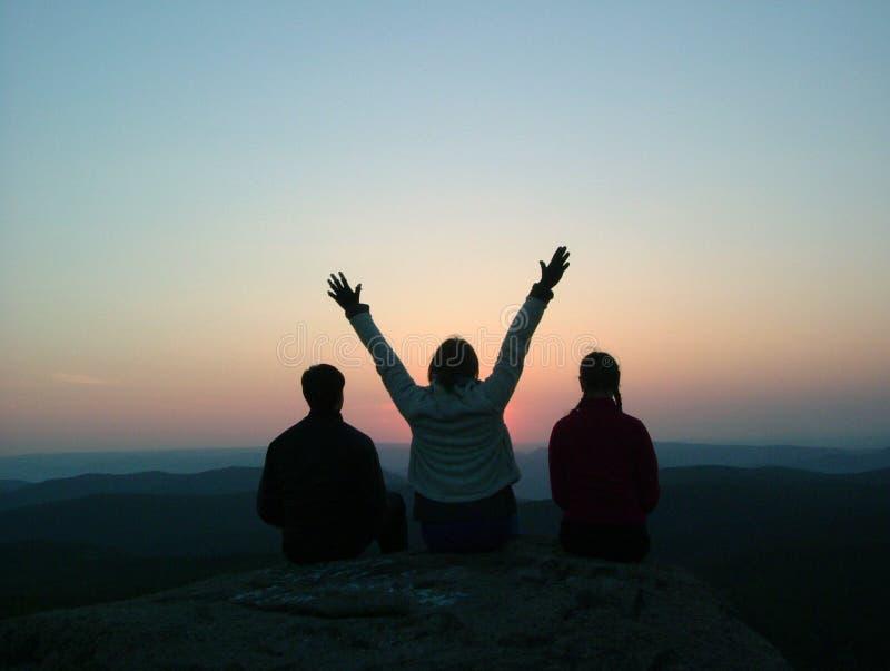 三个朋友坐在山顶部并且享受日落 库存照片