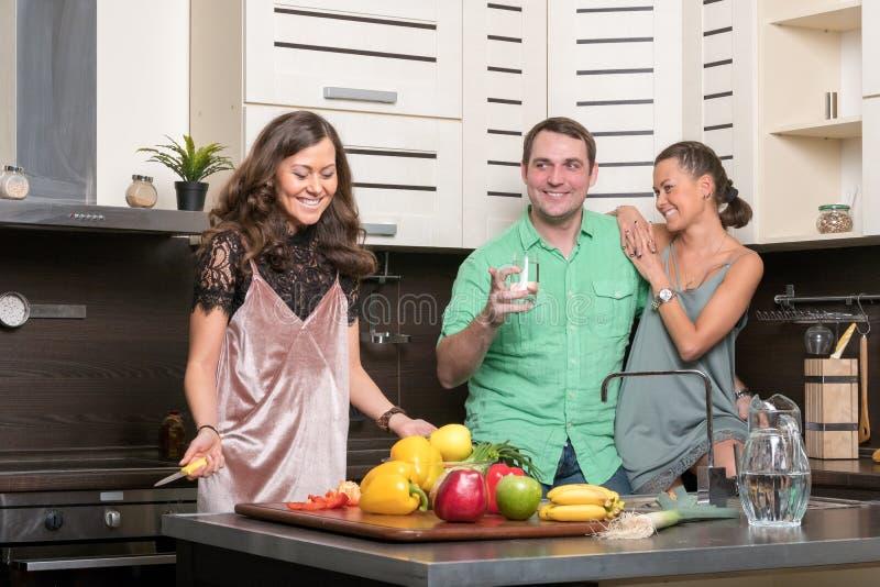 三个朋友获得乐趣在厨房 免版税库存照片
