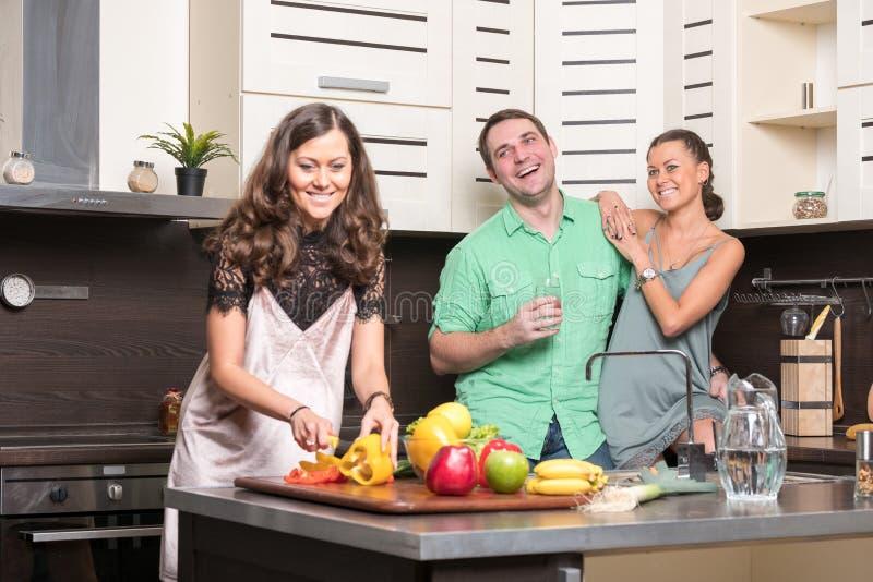 三个朋友获得乐趣在厨房 库存图片