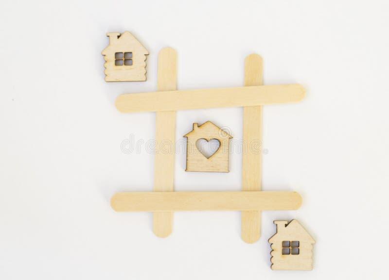 三个木房子在井字游戏比赛连续在,在白色背景的一个栅格 概念家,舒适家 库存照片