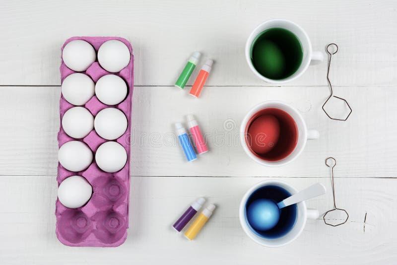 三个杯子染料和鸡蛋与一个纸盒鸡蛋和笔上色的 免版税库存图片