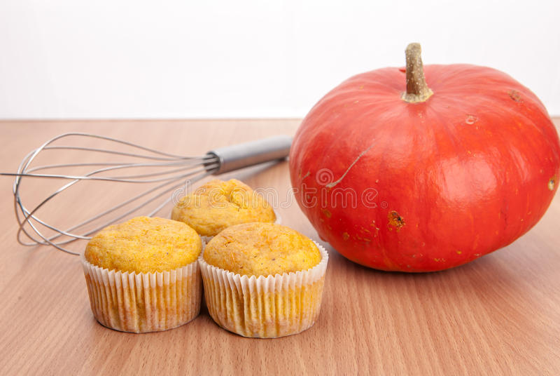 三个杯形蛋糕和南瓜在木纹理桌上 库存照片