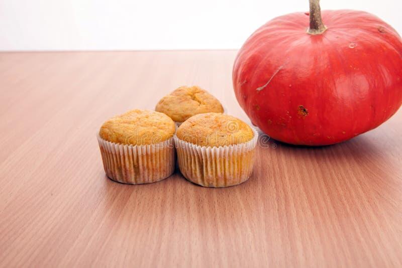三个杯形蛋糕和南瓜在木纹理桌上 免版税库存图片
