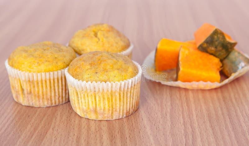 三个杯形蛋糕和南瓜在木纹理桌上 免版税库存照片