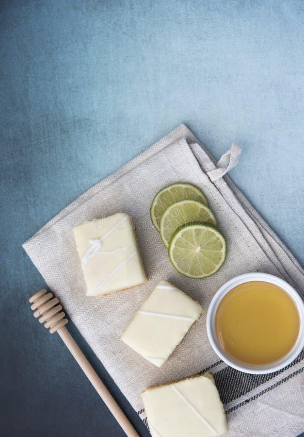 三个柠檬蛋糕切片的垂直的图象与石灰和蜂蜜的 免版税库存照片