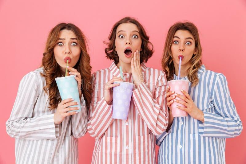 三个深色的女孩20s佩带的休闲衣物饮用的寒冷 免版税库存照片